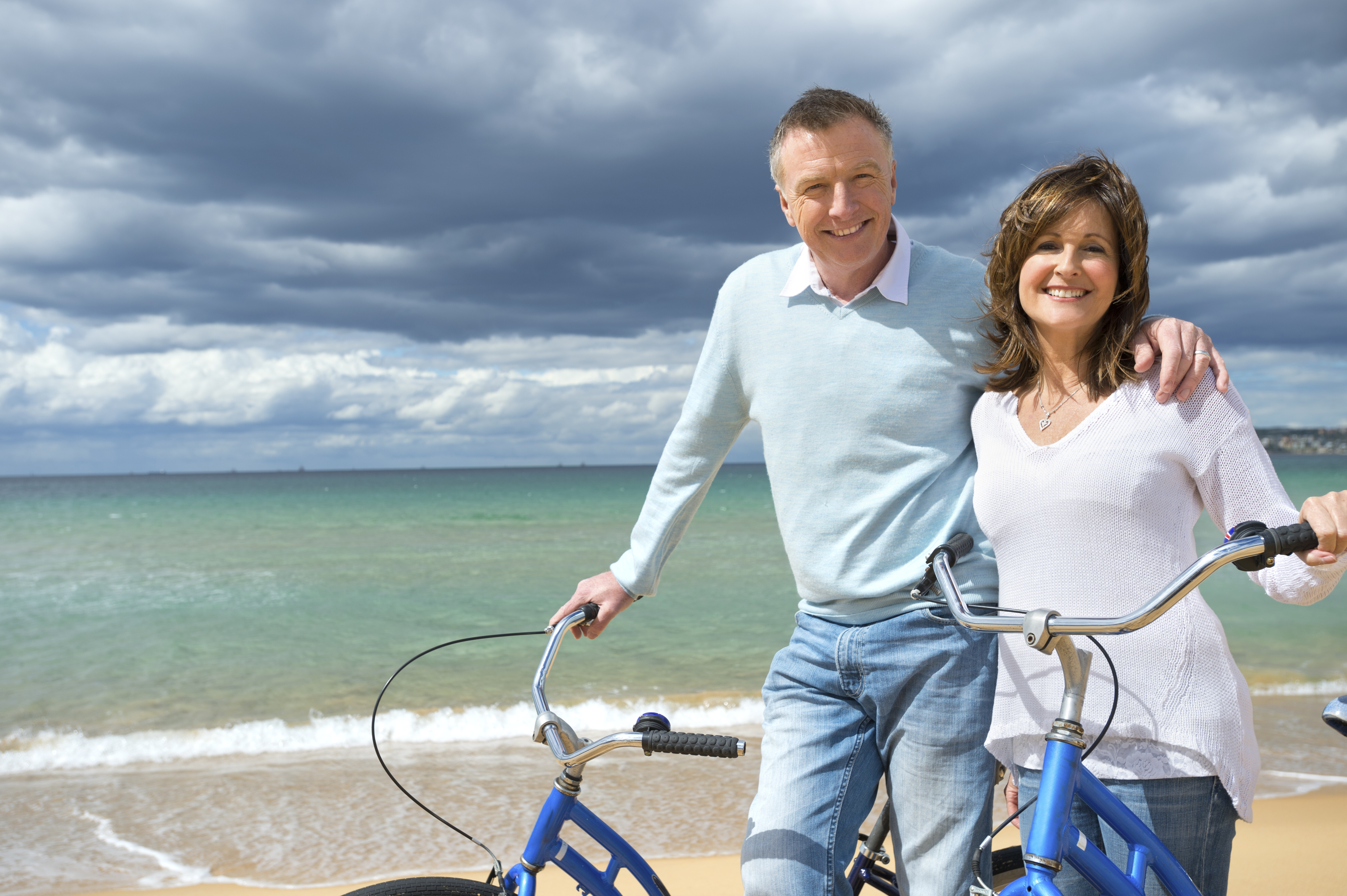 Mature couple cycling on the beach in the sunshine